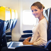 Young woman working on her laptop computer on board of an airplane during the flight — Stock Photo