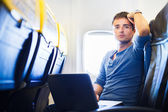 Handsome young man daydreaming while working on his laptop compu — Stock Photo