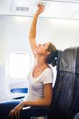 Weibliche beifahrer klimaanlage über ihrem sitzplatz während der anpassung — Stockfoto