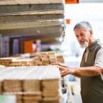 człowiek kupując drewno budowlane w sklepie z materiałami budowlanymi — Zdjęcie stockowe