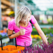 Young woman buying flowers at a garden center — Stock Photo #19796003