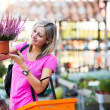 young woman buying flowers at a garden center — Stock Photo #19796023