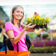 Young woman buying flowers at a garden center — Stock Photo #19796047