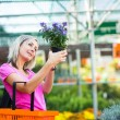 Stock Photo: young woman buying flowers at a garden center