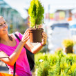 Young woman buying flowers at a garden center — Stock Photo #19796059
