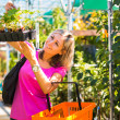 Young woman buying flowers at a garden center — Stock Photo #19796077