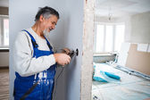 Senior man working on the electrical installations in a freshly — Stock Photo