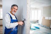 Senior homme travaillant sur les installations électriques dans un fraîchement — Photo