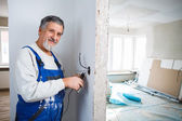 Senior man working on the electrical installations in a freshly — Photo