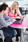 Two college students having fun studying together, using a lapto — Stok fotoğraf