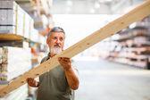 Hombre compra madera de construcción en una tienda de bricolaje — Foto de Stock