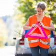 Young female driver wearing a high visibility vest - Stockfoto
