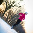 Young woman running outdoors on a cold winter day — Stockfoto