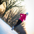 Young woman running outdoors on a cold winter day — Stok fotoğraf
