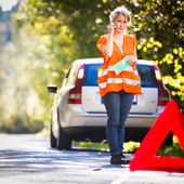 Young female driver wearing a high visibility vest, calling — Stock Photo