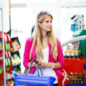 Krásná mladá žena nakupování v supermarketu s potravinami — Stock fotografie