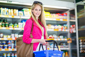 Beautiful young woman shopping in a grocery supermarket — Stok fotoğraf