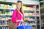 Schöne junge frau, die in einem lebensmittel-supermarkt einkaufen — Stockfoto