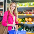 Beautiful young woman shopping for fruits and vegetables - Foto de Stock  