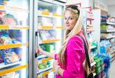 Beautiful young woman shopping in a grocery supermarket — Foto de Stock