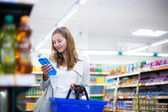 Beautiful young woman shopping in a grocery supermarket — Stock Photo