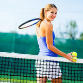 Portrait of a pretty young tennis player on the court — Stok fotoğraf