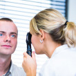 Optometry concept - handsome young man having her eyes examined - Stock Photo