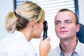 眼科视光学概念-英俊的年轻男子有审查她的眼睛 — 图库照片