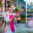 Young woman buying flowers at a garden center — Stock Photo #22660199