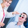 Optometry concept - handsome young man having his eyes examined - Stock Photo