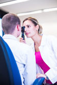Optometry concept - handsome young man having her eyes examined — Foto Stock