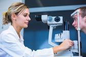 Concetto di optometria - bel giovane, avendo esaminati gli occhi — Foto Stock