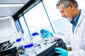 Starší muž výzkumník provádění vědeckého výzkumu v laboratoři — Stock fotografie