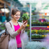 Young woman buying flowers at a garden center — 图库照片
