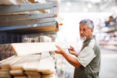 Senior man buying construction wood in a DIY store — Stock Photo