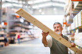 Senior man buying construction wood in a DIY store — Foto de Stock
