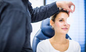 Optometry concept - pretty young woman having her eyes examined — Stock fotografie