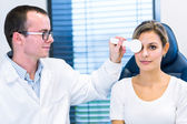 Optometry concept - pretty young woman having her eyes examined — 图库照片