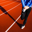 Young woman stretching before her run casts a shadow on the track — Stock Photo #23458926