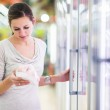 Young woman shopping for meat in a grocery store — Stock Photo #23458960