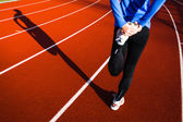 Young woman stretching before her run casts a shadow on the track — Stock Photo