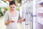 年轻女子为肉在一家杂货店购物 — 图库照片