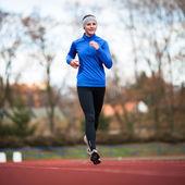 Atletizm stadı'nda çalışan genç bir kadın — Stok fotoğraf