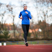 Young woman running at a track and field stadium — Stok fotoğraf
