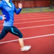 Young woman running at a track and field stadium - Foto Stock