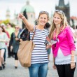 Two female tourists walking along the Charles Bridge while sight — Stock Photo #23461254