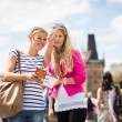 Two female tourists walking along the Charles Bridge while sight — Foto Stock #23461822