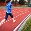 Young woman running at a track and field stadium — Stockfoto