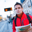 Just arrived: handsome young man studying a map on a bus stop — Stock Photo #23461952