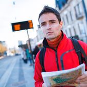 Just arrived: handsome young man studying a map on a bus stop — Stockfoto
